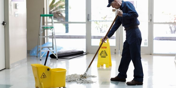 Senior adult Janitor keeps the floors cleaned and sanitized due to the virus.